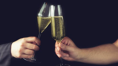 Crop anonymous couple clinking sparkling fine champagne glasses of stylish design against black background