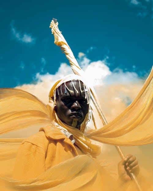 Man in Yellow Robe Under Blue Sky
