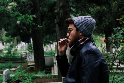 Man Smoking Cigarette Near Green Leaf Tree