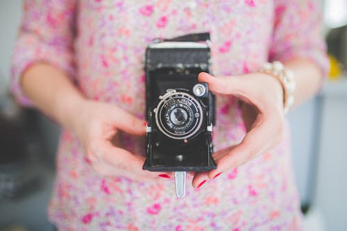 Old analog camera in woman's hands
