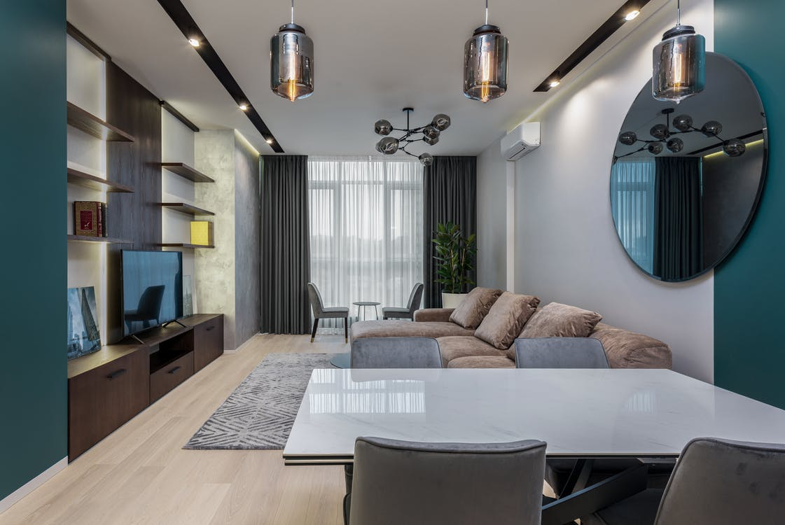 Spacious living room interior with wooden furniture and soft sofa