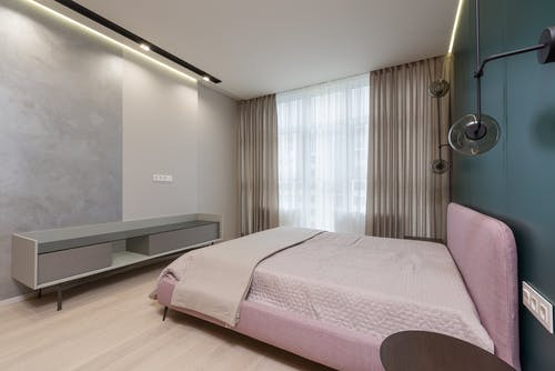 Interior of bedroom with minimalist wooden furniture and comfortable bed placed near wall with creative lamps