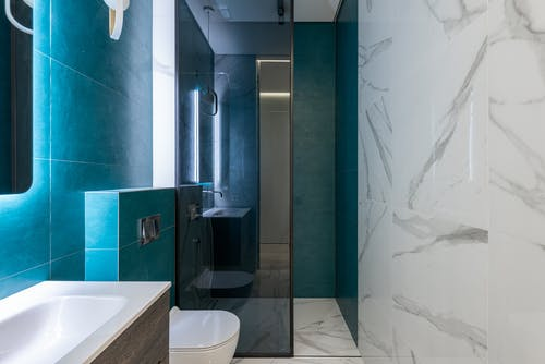 Interior of modern bathroom with shower cabin and bright illumination