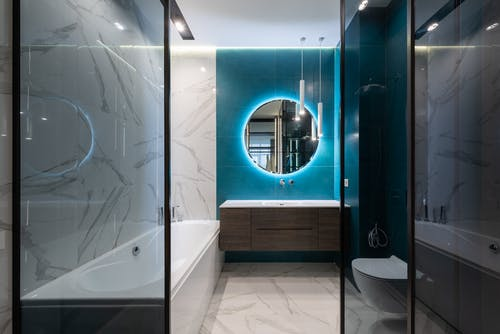 Round mirror with neon illumination hanging over sink in modern bathroom with white ceramic toilet bowl and bathtub