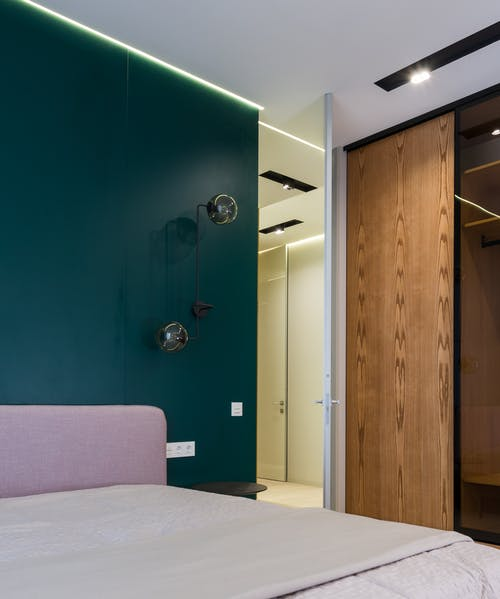 Comfortable bed with coverlet placed near wooden wardrobe in modern apartment in daylight