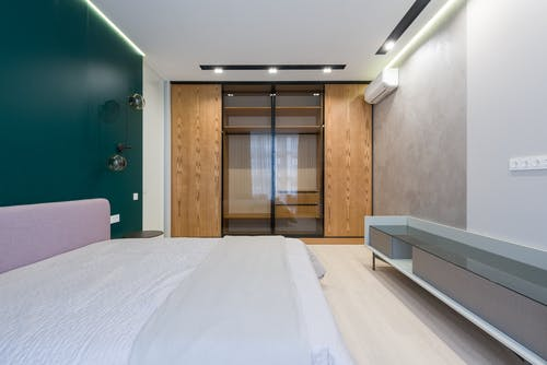Cozy bed and wardrobe with wooden and glass doors in modern bedroom