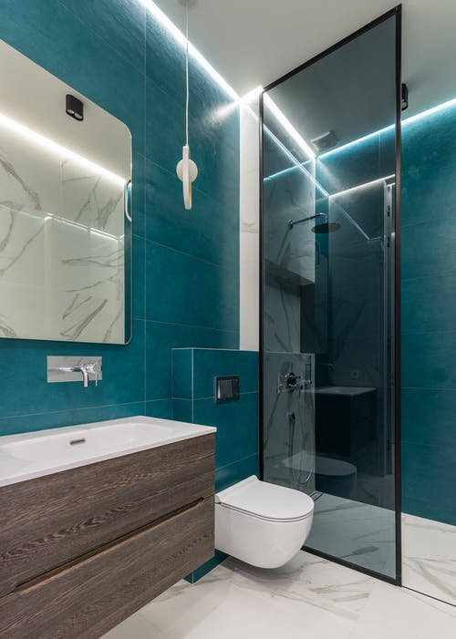 Interior of modern bathroom with glass shower cabin ceramic sink and mirror hanging on blue tiled wall