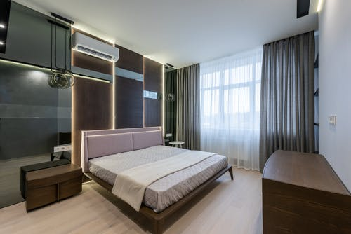Wooden furniture and bed in contemporary apartment in daylight
