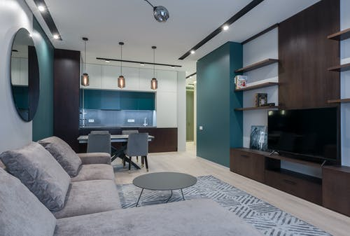 Interior of modern studio apartment with kitchen zone and living room with comfy sofa and TV set placed on wooden cabinet