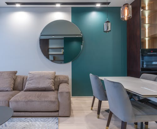 Round mirror hanging above sofa in contemporary apartment