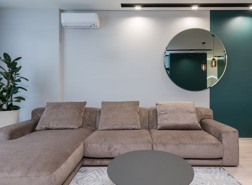 Round mirror hanging on wall above big comfortable sofa in spacious living room of modern apartment