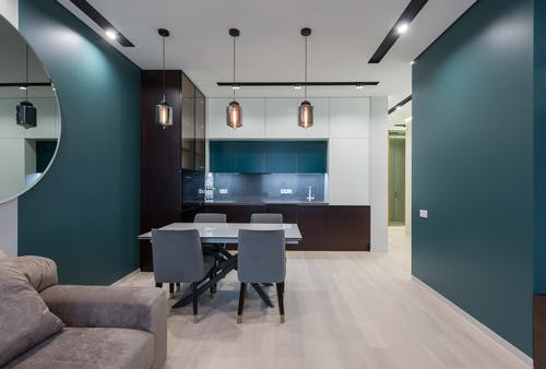 Dining table with chairs in kitchen near comfy sofa in modern studio apartment with creative design