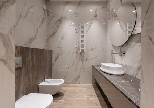 Interior of light modern bathroom with bidet and toilet and sink on cabinet under round mirror on tile