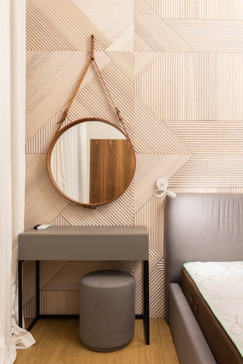 Bedroom interior with mirror and table with pouf near bed