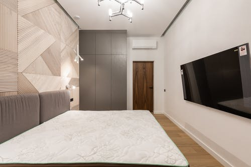 Interior of modern light hotel room with TV on wall near bed and cabinet near door
