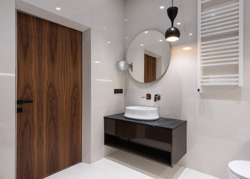 Interior of modern bright bathroom with sink on counter under round mirror near toilet and lamp hanging from ceiling near door