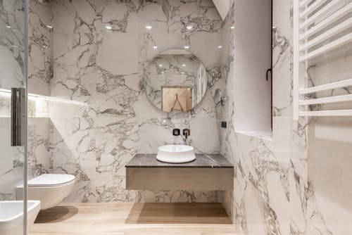 Interior of modern bathroom with round mirror hanging on marble wall and white ceramic sink and toilet bowl
