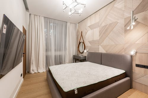 Interior of cozy bedroom decorated with white curtains and creative lamps