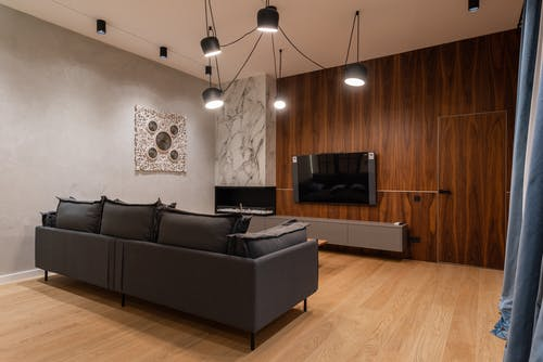 Modern TV hanging on wooden wall in front of comfortable couch in spacious stylish living room