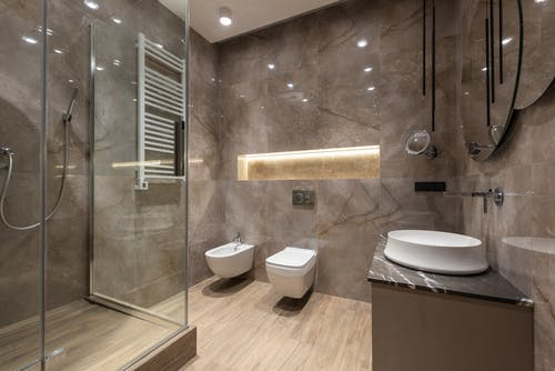 Spacious bathroom interior with shower cabin and shiny tiled walls