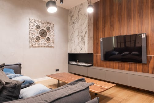 Flat screen TV hanging on wooden wall near fireplace against soft sofa with cushions in modern apartment