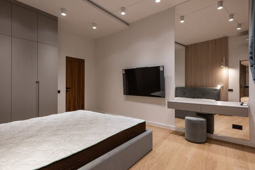 Comfortable bed and wardrobe in modern bedroom placed in front of TV hanging on wall near dressing table with big mirror