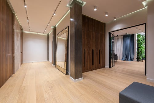 Interior of spacious hallway of modern apartment with wooden walls and floor and big doorway