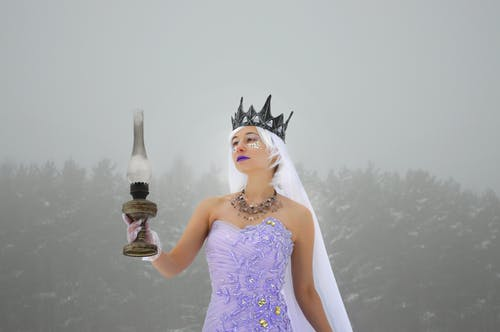Female in crown and dress holding kerosene lamp in winter