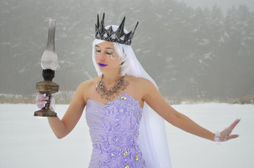 Elegant young woman wearing purple dress and crown with white veil and gloves with old kerosene lamp in hand on snowy meadow near woods