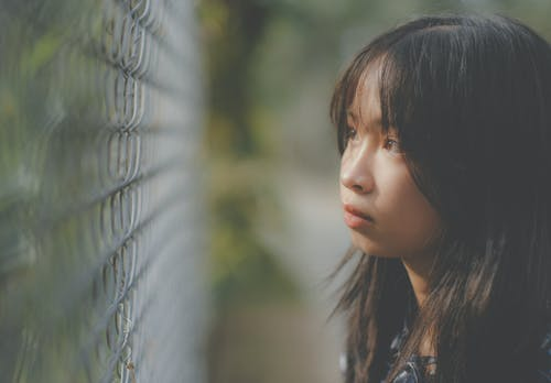 Side view of serious ethnic girl with long dark hair and brown eyes looking through metal fence