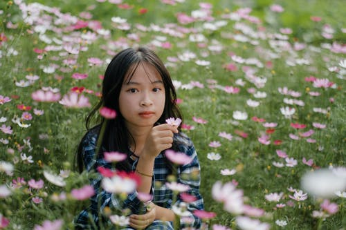 Charming Asian girl with bud of blooming flower