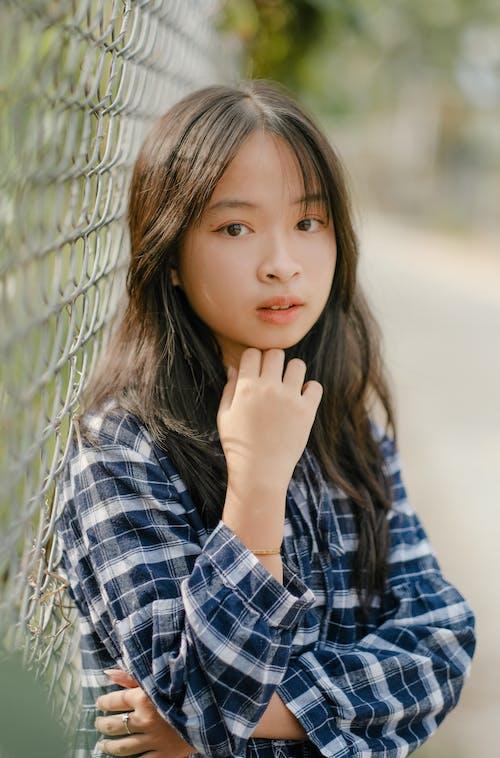 Cute Asian girl touching chin standing near net