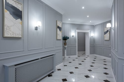 Interior of corridor of contemporary villa with shiny tiled floor and gray walls decorated with paintings and lamps