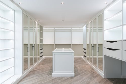 Interior of spacious walk in closet with mirrored furniture and bright lamps
