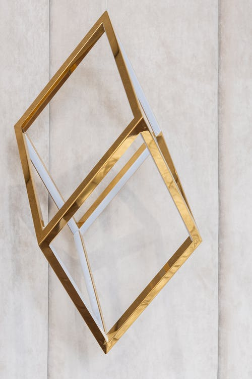 Golden metal geometric cube shaped decor hanging on gray wall in modern apartment