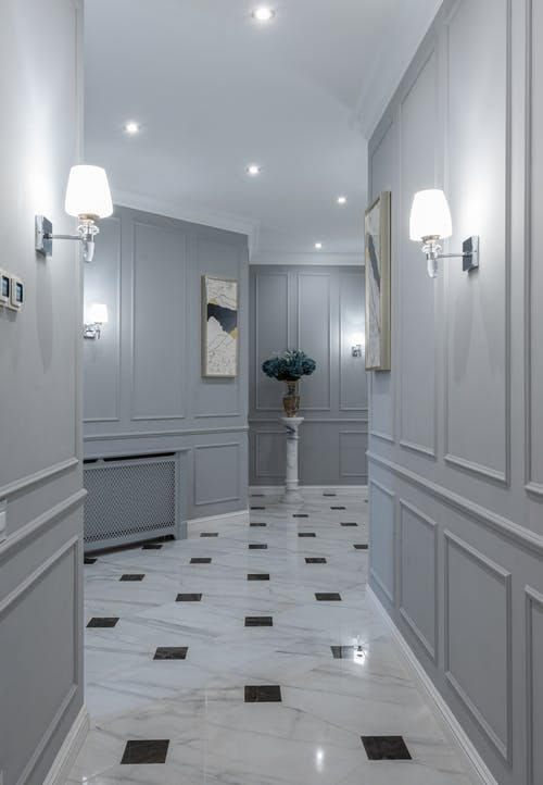 Elegant shining lamps and paintings hanging on gray walls in hallway of classic styled house with marble floor