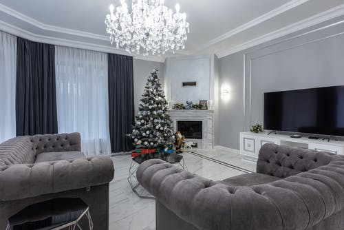 Spacious living room with comfy couch and armchair decorated with Christmas tree