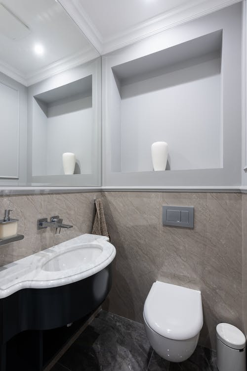 Marble sink and ceramic toilet in modern bathroom with mirror and tiled walls