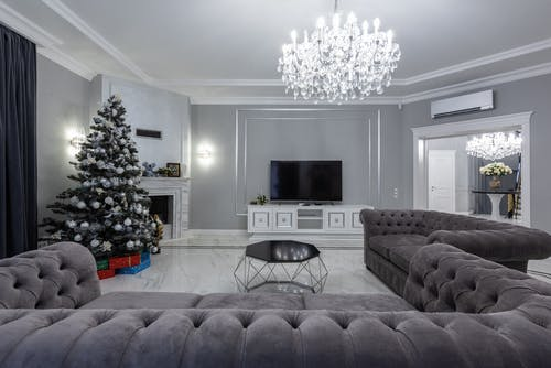 Contemporary spacious living room with glowing massive chandelier and modern TV near geometrical table