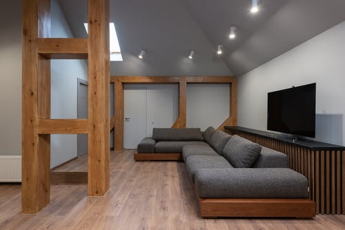 Interior of cozy prestige living room with spacious soft gray sofa illuminated with bright lamps