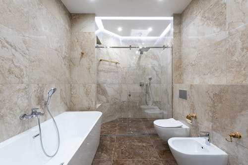 Interior of contemporary bathroom with marble walls and comfortable shower cabin under bright light of lamp