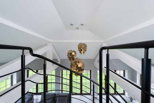 Interior of modern living room with shimmering golden pendant lamps in living room with metal stairs