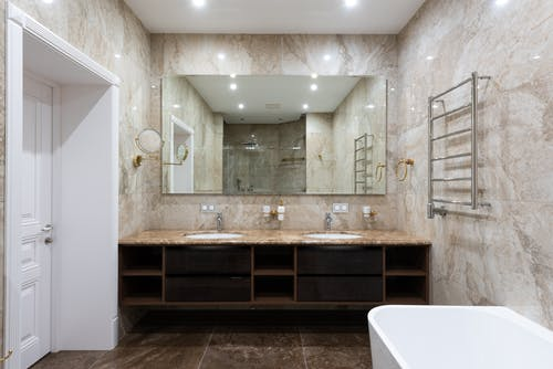 Interior of contemporary bathroom with marble walls and white clean sinks under bright glowing lamps