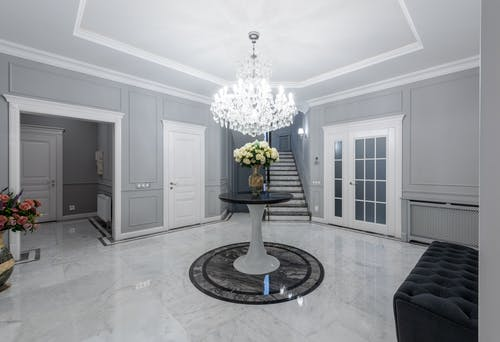 Interior of modern hall with glowing chandelier and soft sofa on sparkling clean floor