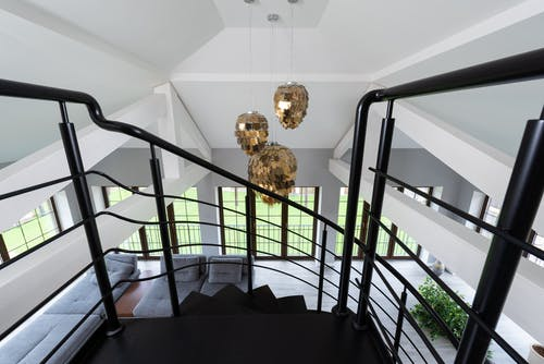 Modern black stairs leading to lounge with soft sofas