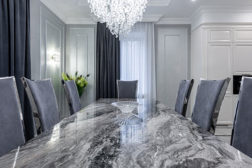 Interior of contemporary dining room with stylish marble table and comfortable chairs in light apartment in daytime