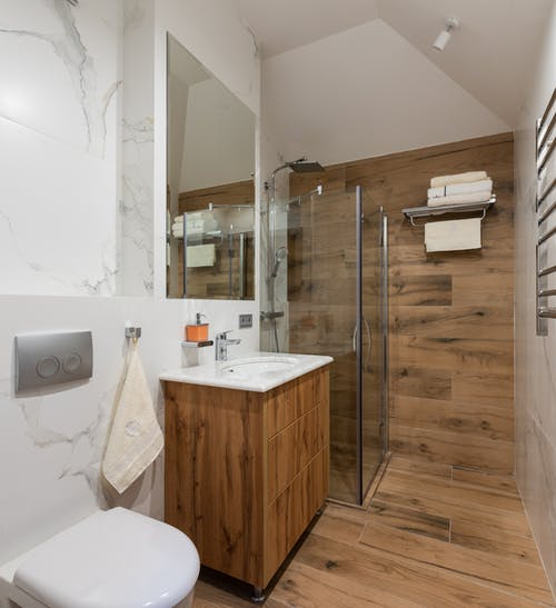 Interior of stylish clean bathroom with wooden elements and light walls in modern apartment