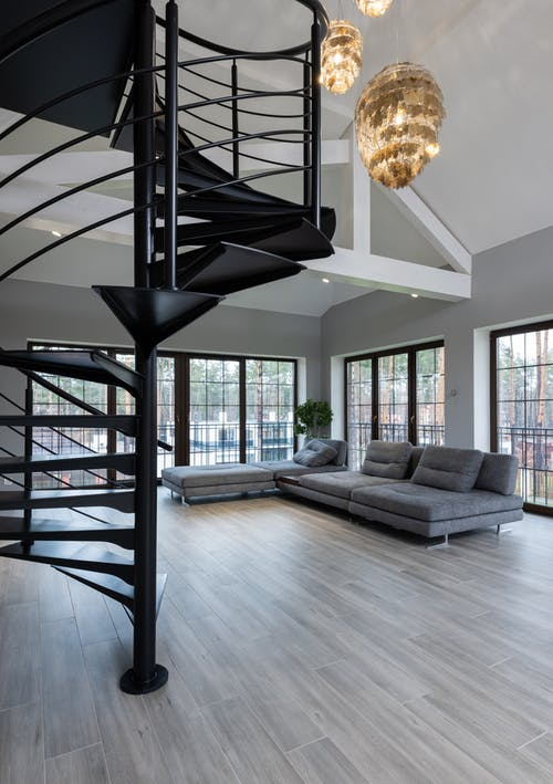 House interior with spiral staircase near couch and windows