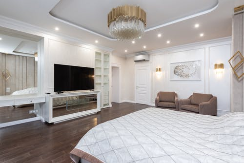 Interior of luxury bedroom with big bed and armchairs at wall and TV on cabinet under chandelier