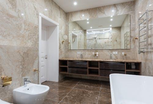 Bathroom with bidet and bathtub near sink on counter